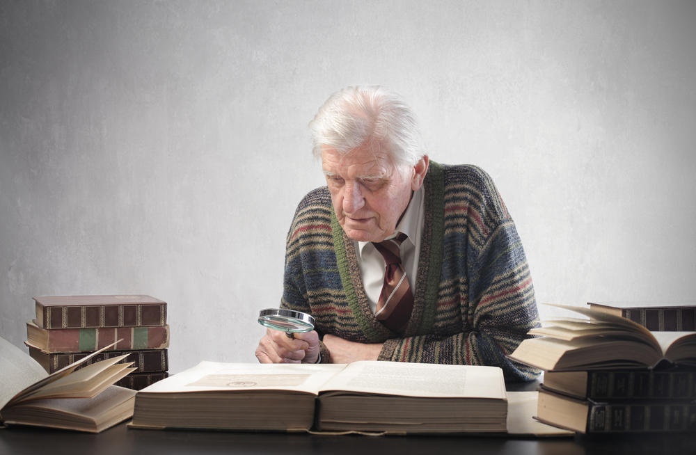 old man at his desk with books